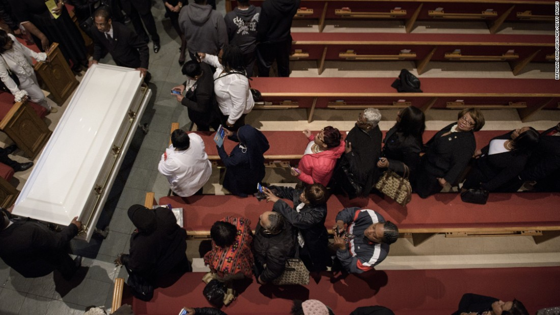 People watch as Gray's casket is carried out of the church.