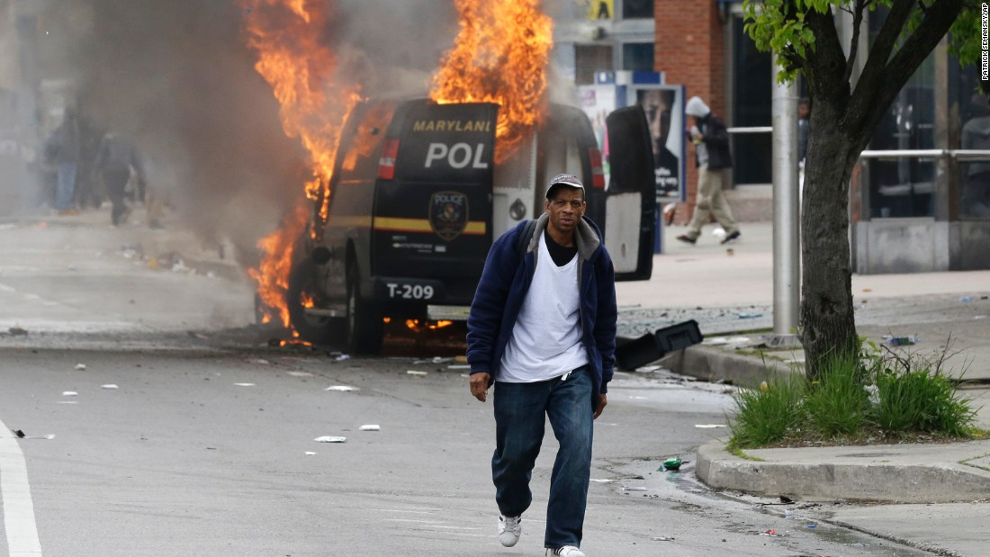 A man walks past a burning police vehicle on April 27.