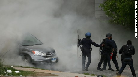 Baltimore Police officers use tear gas to disperse protesters outside the Mondawmin Mall following the funeral of Freddie Gray on April 27, 2015, in Baltimore, Maryland.