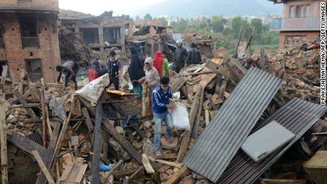 People carry their belongings amidst the rubble of collapsed houses in Bhaktapur, on the outskirts of Kathmandu, on April 27, 2015, two days after a 7.8 magnitude earthquake hit Nepal.