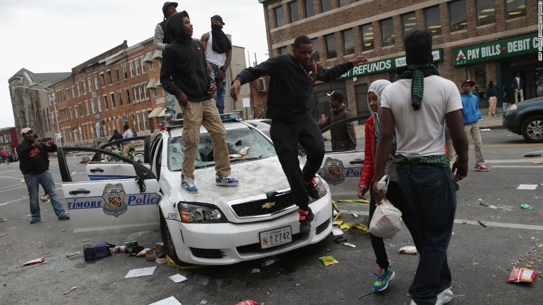 Demonstrators climb on a destroyed Baltimore Police car in the street near the corner of Pennsylvania and North avenues during violent protests following the funeral of Freddie Gray on April 27, 2015, in Baltimore, Maryland.