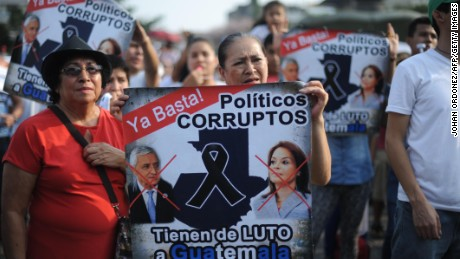 Demonstrators hold signs during a protest against Guatemalan President Otto Perez Molina and Vice President Roxana Baldetti for the recent corruption cases in the government, in Guatemala City on April 25, 2015.