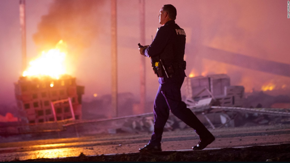 A police officer walks by a burning building on April 27.