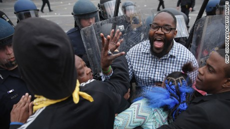 A man shouts for calm as protesters clash with police April 27.