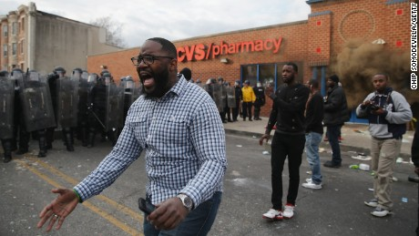 BALTIMORE, MD - APRIL 27: A man shouts calm as protesters face off with Baltimore Police as a CVS pharmacy burns at the corner of Pennsylvania and North avenues during violent protests following the funeral of Freddie Gray April 27, 2015 in Baltimore, Maryland. Gray, 25, who was arrested for possessing a switch blade knife April 12 outside the Gilmor Homes housing project on Baltimore's west side. According to his attorney, Gray died a week later in the hospital from a severe spinal cord injury he received while in police custody. (Photo by Chip Somodevilla/Getty Images)