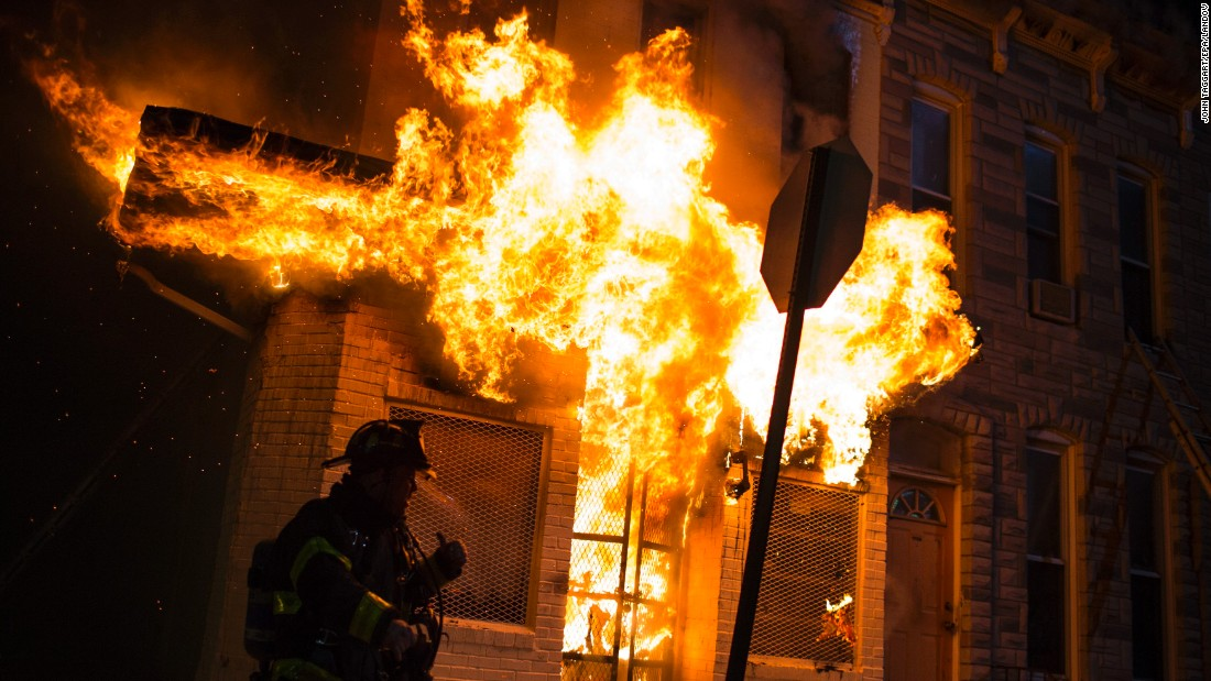 Firefighters respond to a burning building during the riots late April 27.