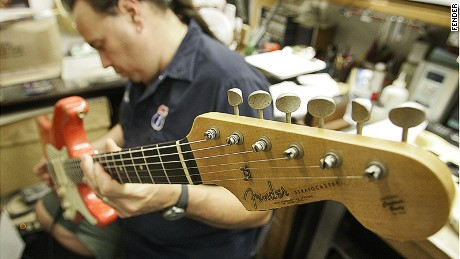 A guitar builder puts the final touches on a Stratocaster, the axe of choice for rockers (and wannabes) the world over.