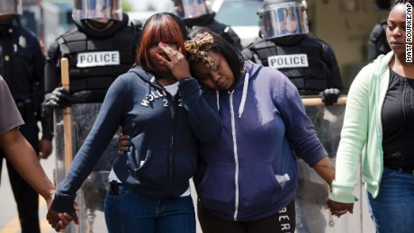"""Jerrie Mckenny, left, and her sister Tia Sexton embrace as demonstrators hold hands and sing the hymn """"Amazing Grace"""" in the streets of Baltimore on Tuesday, April 28."""