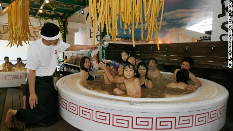 HAKONE, JAPAN: Clad in chef costume, an employee (L) of Hakone Kowakien Yunessun put noodle-shaped bath articles into a 2-meter wide bathtub modeled Chinese noodle bowl in Hakone, 100km west of Tokyo, 14 July 2007. The hot spring leisure facility opened the 'Ramen Bath', or Chinese noodle bath, as a main feature for summer vacation season until 26 September. AFP PHOTO/Toru YAMANAKA (Photo credit should read TORU YAMANAKA/AFP/Getty Images)