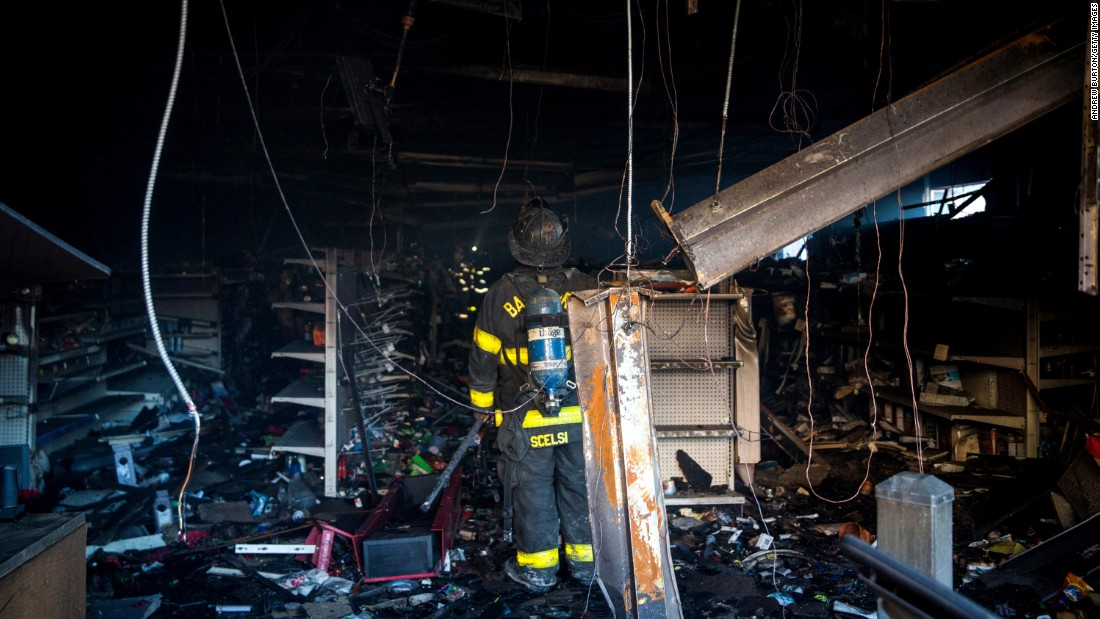 Baltimore firefighters inspect a burned store on April 28.