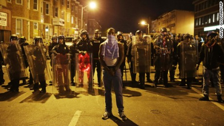 A man stands in front of a line of police officers in riot gear as part of a community effort to disperse the crowd ahead of a 10 p.m. curfew in the wake of Monday's riots following the funeral for Freddie Gray, Tuesday, April 28, 2015, in Baltimore. (AP Photo/David Goldman)