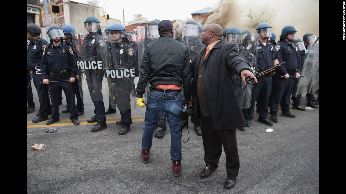 "A man attempts to calm a fellow demonstrator as they face police in Baltimore on April 27, 2015. Riots broke out after <a href=""http://www.cnn.com/2015/04/27/us/gallery/freddie-gray-funeral/index.html"">the funeral for Freddie Gray</a>, who died of a severe spinal cord injury while in police custody. His death sparked <a href=""http://www.cnn.com/2015/04/23/us/gallery/freddie-gray-protest/index.html"">protests in Baltimore</a> and raised long-simmering tensions between police and residents."