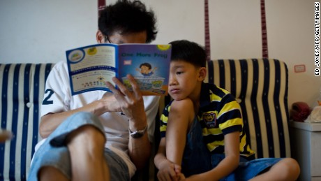 To go with China-education-society, FEATURE by Tom Hancock In a photo taken on July 31, 2012 eight-year-old Zhang Hongwu reads with his father Zhang Qiaofeng during his home schooling at their apartment in Beijing. Giving up his successful career as the head of a medical research firm to spend his days at home reading from children's story books was a tough choice for Chinese father Zhang Qiaofeng.    AFP PHOTO / Ed Jones        (Photo credit should read Ed Jones/AFP/GettyImages)