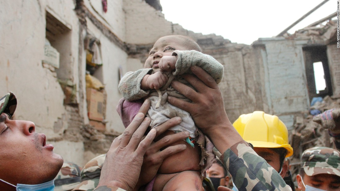 Four-month-old Sonit Awal is held up by Nepalese army soldiers after being rescued from the rubble of his house in Bhaktapur, Nepal, on April 26.