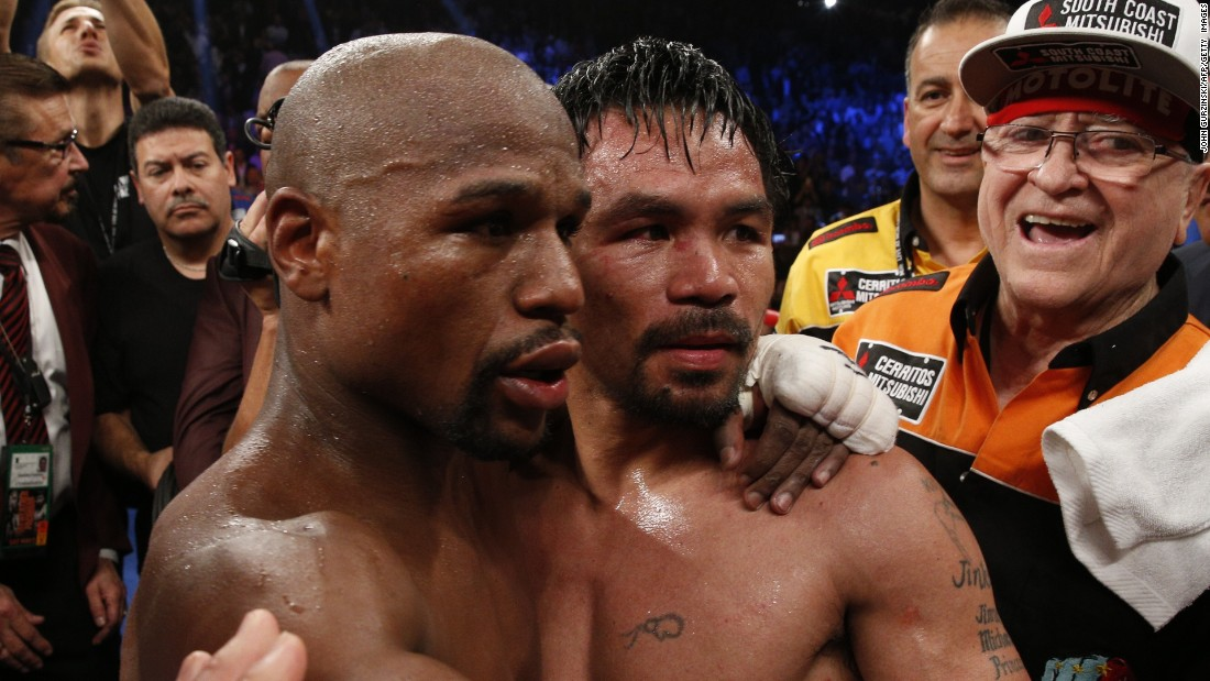 Mayweather left, hugs Pacquiao after defeating him in their welterweight unification bout.
