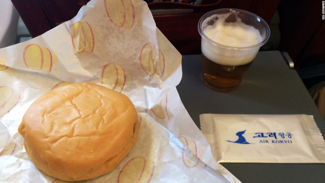 The inflight meal consists of a burger and glass of North Korean beer.