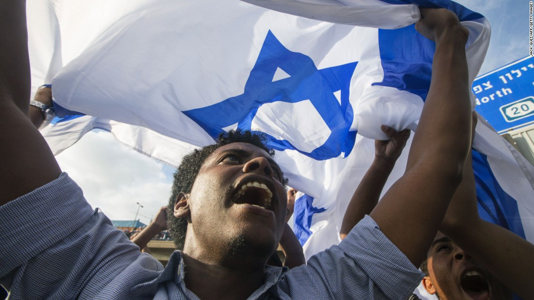 A protester carries an Israeli flag during the demonstration.