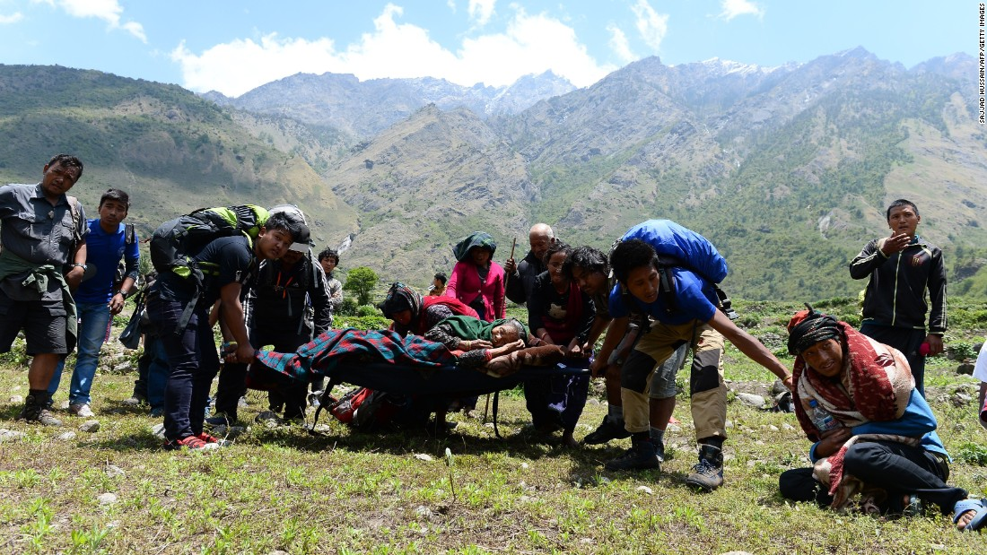 An injured Nepalese woman is carried by villagers toward an Indian army helicopter to be airlifted from Philim village in Gorkha district in Nepal on May 3.