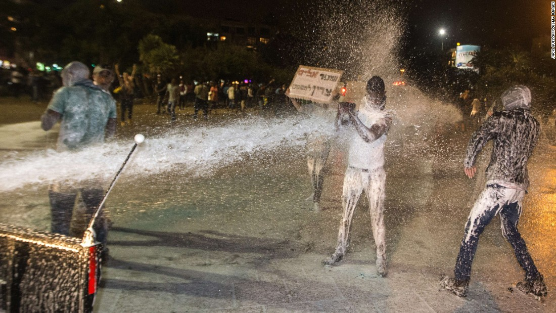 Israeli police use a water cannon against protesters Sunday evening. The soldier in the video, Damas Fekadeh, has called for calm and restraint.