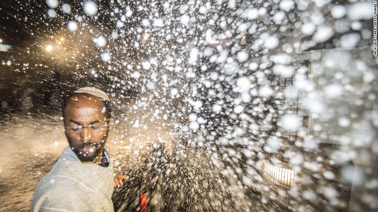 A protester is hit by the spray from a water cannon. The Tel Aviv protest comes on the heels of a largely peaceful demonstration in Jerusalem on Thursday that drew more than 1,000 people.