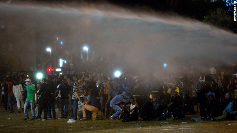 Protesters in Tel Aviv are hit by a water cannon as they clash with Israeli riot police during a protest against racism and police brutality on May 3.