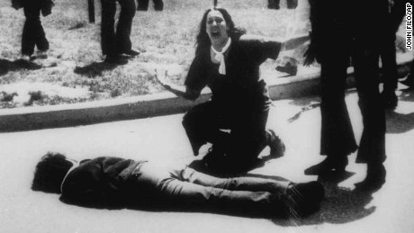 """*** FILE *** Mary Ann Vecchio gestures and screams as she kneels by the body of a student lying face down on the campus of Kent State University, Kent, Ohio on May 4, 1970. A static-filled recording was released Tuesday May 1, 2007 of the 1970 Kent State University shooting that killed four students raising questions not only about whether someone called on National Guardsmen to fire, but also who might have given the order. The tape was released by Alan Canfora, 58, one of nine students wounded in the 1970 shootings. He played two versions of the tape _ the original and an amplified version _ in which he says a Guard officer issues the command, """"Right here! Get Set! Point! Fire!""""  (AP Photo/John Filo)"""