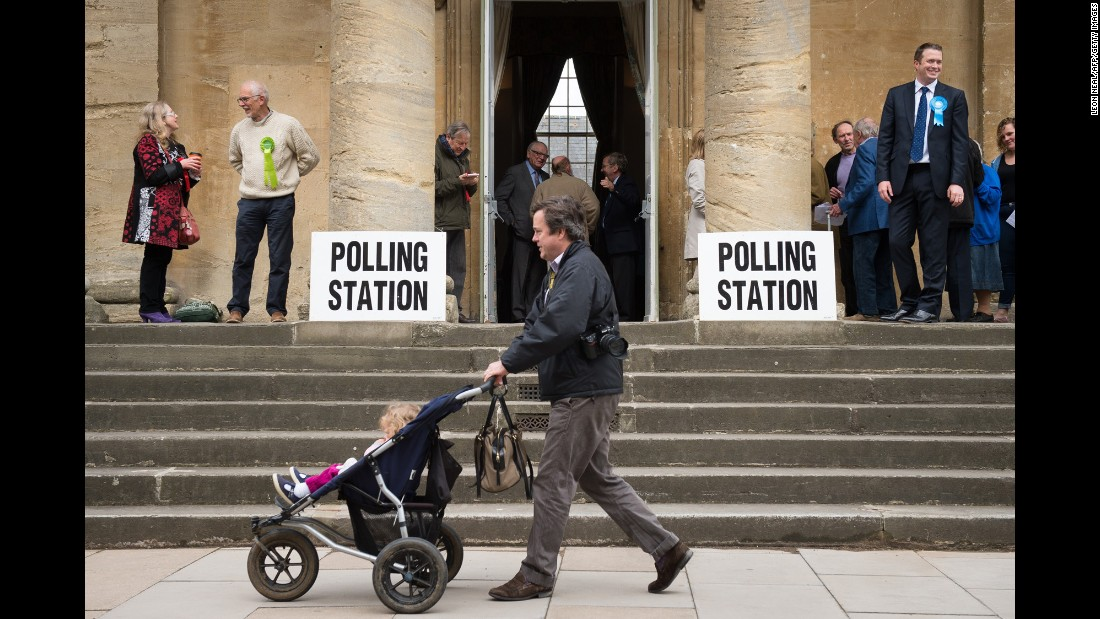 People arrive at a polling station in Chipping Norton, England, to cast their votes.