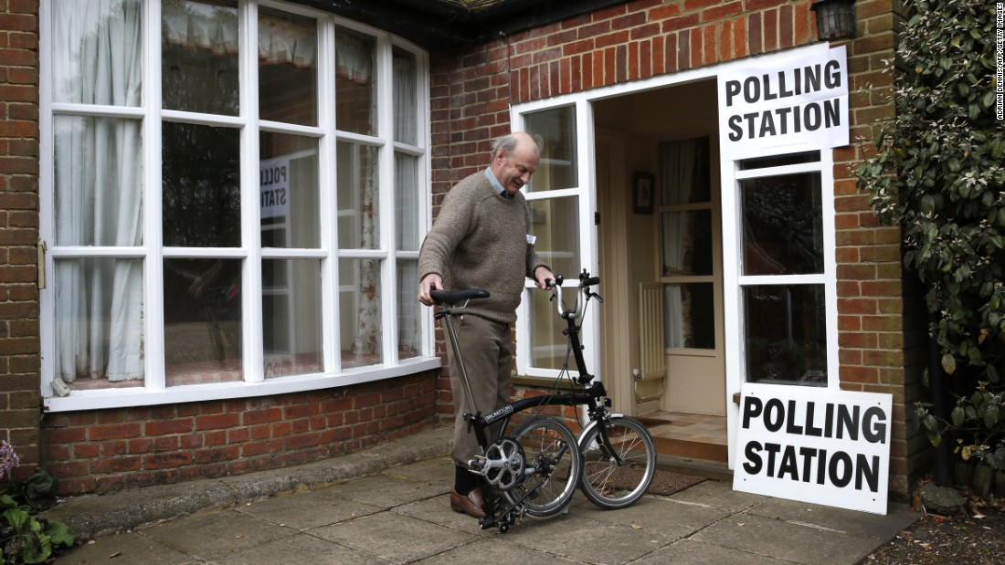 A member of the public unfolds his bike after voting at Three Oaks, a residential house turned polling station, in Bramshill, England.