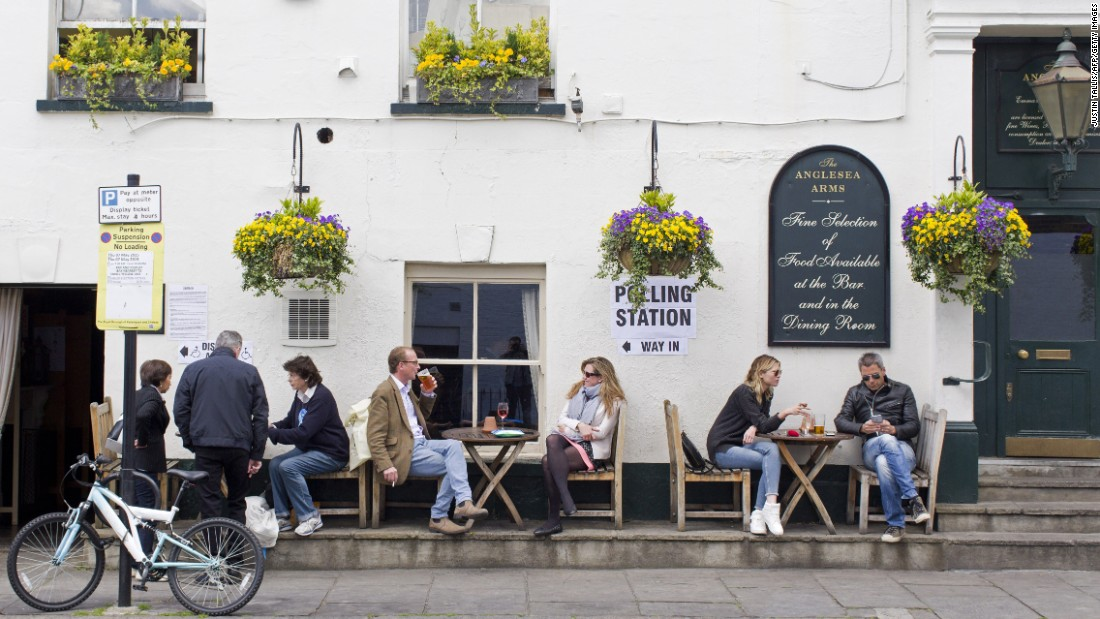 People sit outside the Anglesea Arms pub in London. The pub is being used as a polling station.