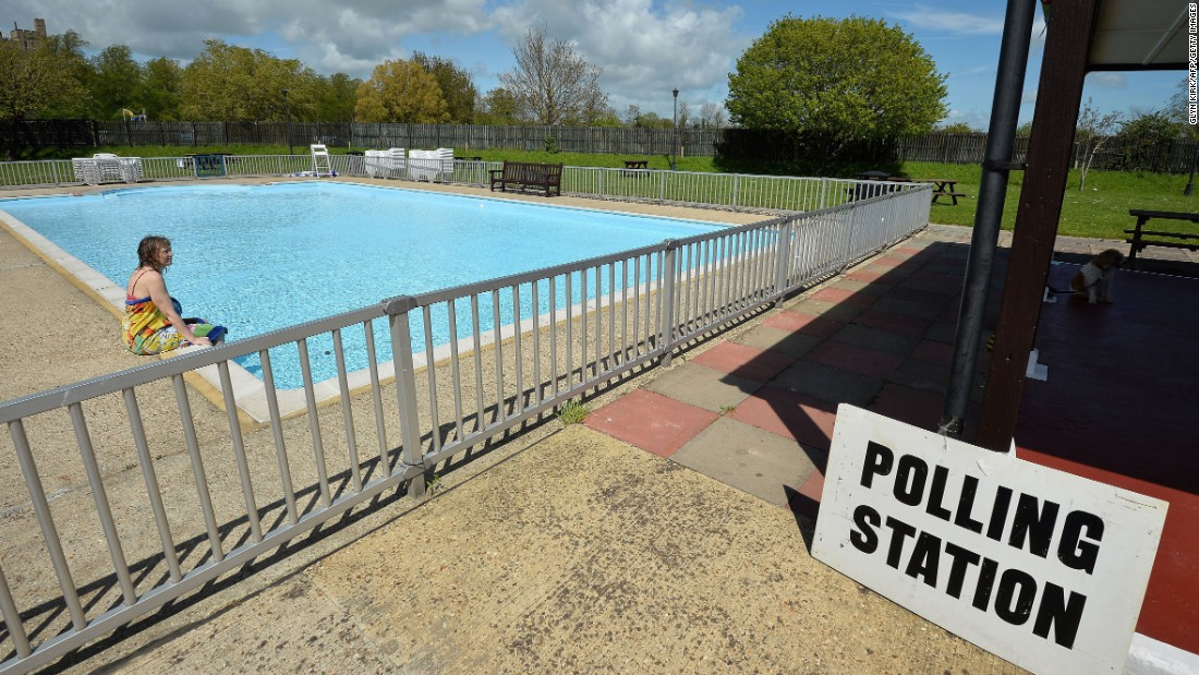 A woman sits by a swimming pool at a temporary polling station in Arundel, England.