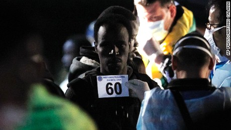 Migrants have identification photos taken as they disembark from the Italian Financial Police ship Monte Cimone at Catania's harbor, Sicily, Italy, on May 6, 2015.