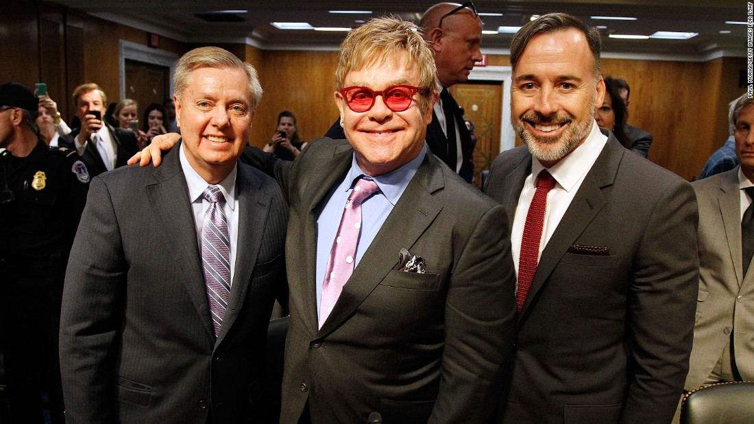 Graham; Sir Elton John, center; and filmmaker and John's husband, David Furnish, pose after testimony at a U.S. Senate hearing on the global fight against AIDS on May 6, 2015. Graham and Democratic Sen. Patrick J. Leahy of Vermont hosted John as part of their bipartisan effort to combat HIV infection.