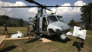 Nepalese military service members unload supplies from a UH-1Y Huey in Charikot, Nepal, May 5, Nepal, May 5.