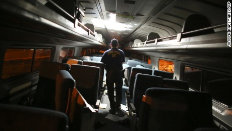 A crime scene investigator looks inside a train car.