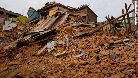 A man stands on debris in Chautara, Nepal, on Wednesday, May 13.