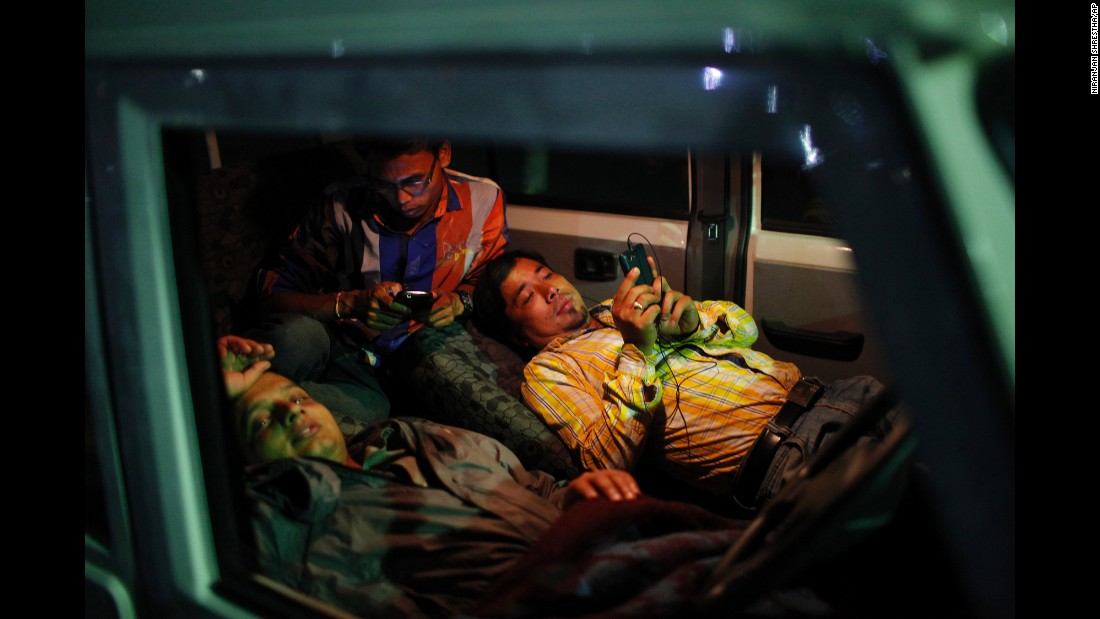 People take shelter inside a car instead of being indoors in Kathamandu on May 12.