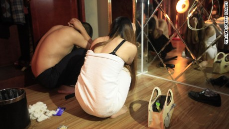 This picture taken late on February 9, 2014 shows an alleged sex worker and client during a raid on an entertainment center in Dongguan, southern China's Guangdong province. A total of 67 people were arrested and 12 entertainment venues involved in the illegal sex trade were shut down after China Central Television (CCTV) revealed a dozen hotels in Dongguan offered sex services. CHINA OUT AFP PHOTO (Photo credit should read STR/AFP/Getty Images)