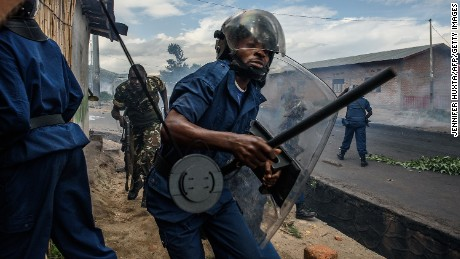 Burundi's policemen and army forces run after protestors throwing stones during a demonstration against incumbent president Pierre Nkurunziza's bid for a 3rd term on 13 May 2015 in Bujumbura.