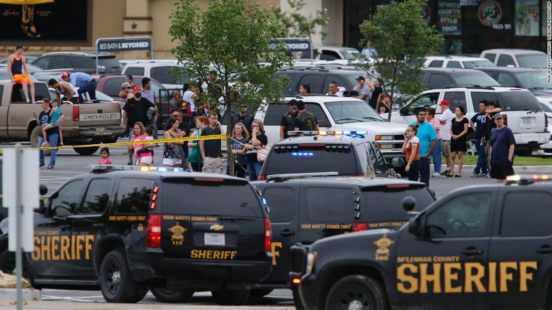 People in Waco, Texas, stand near the parking lot of a Twin Peaks restaurant where nine people were killed in a shooting on Sunday, May 17. At least 18 people were hospitalized as well after a melee between rival biker gangs.