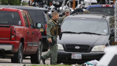 A law enforcement officer walks through the parking lot near the scene of the shooting.