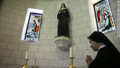 A sister prays in front of relics of Marie Alphonsine Ghattas at the Mamilla monastery in Jerusalem on May 12, 2015, a few days ahead of the canonisation of the Palestinian nun in Rome.