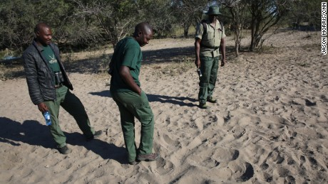 Trackers search for rhino prints near a watering hole.