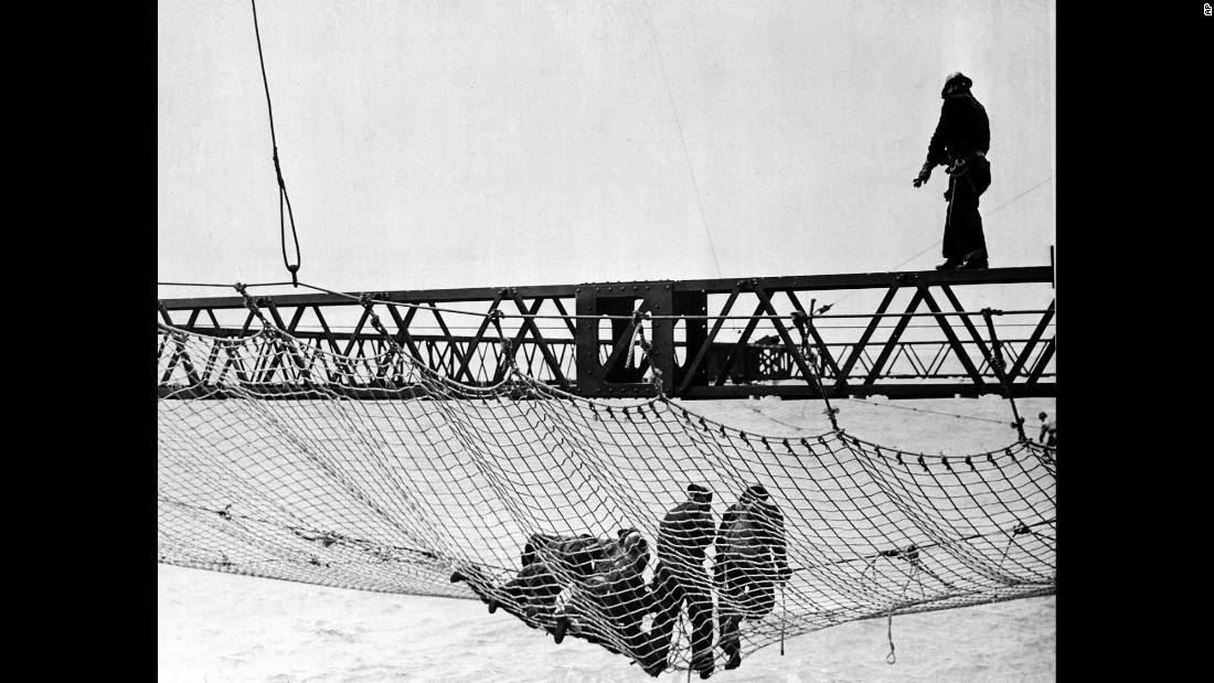 Workers in 1935 install the first section of a huge safety net, at a cost of $98,000, that extended beneath the bridge from shore to shore. The netting was added to catch workers who tumbled off their precarious steel perches above.
