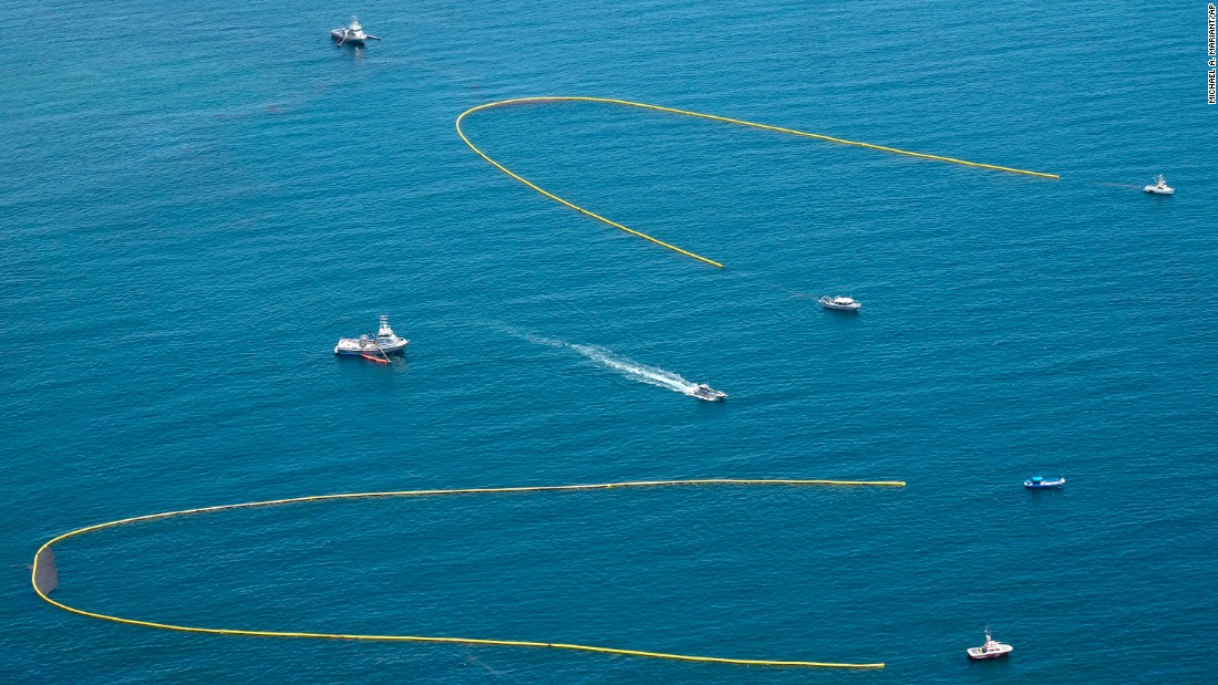 Ships pulling booms attempt to collect oil from the spill on May 20.