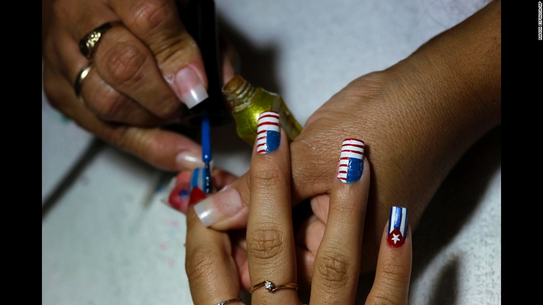 A woman has her nails painted in the likeness of the Cuban and U.S. flags inside her Havana home in December.