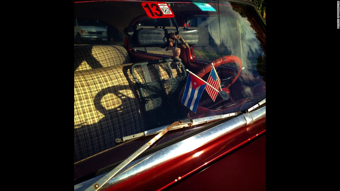 Cuban and U.S. flags decorate the dashboard of a car in Havana.