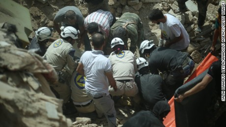 ALEPPO, SYRIA - MAY 20: Syrian emergency services personnel accompanied with Syrian local people remove the body of a Syrian from the rubble of buildings following a reported barrel bomb attack by government forces on the Qadi Askar district of the northern Syrian city of Aleppo on May 20, 2015. (Photo by Salih Mahmud Leyla/Anadolu Agency/Getty Images)