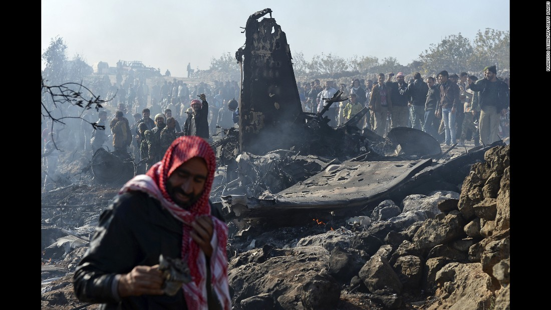 Rebels celebrate next to the remains of a Syrian government fighter jet that was shot down at Daret Ezza, on the border of the provinces of Idlib and Aleppo, on November 28, 2012.