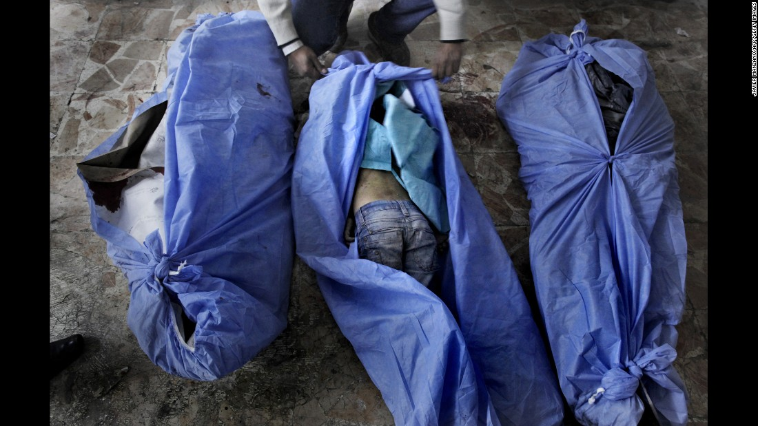 The bodies of three children are laid out for identification by family members at a makeshift hospital in Aleppo on December 2, 2012. The children were allegedly killed in a mortar shell attack that landed close to a bakery in the city.