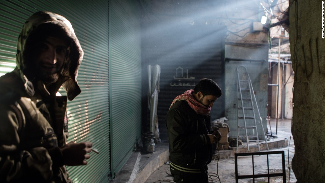 A rebel fighter prepares the wires of a car-mounted camera used to spy on Syrian government forces while his comrade smokes a cigarette in Aleppo's Bab al-Nasr district on January 7, 2013.